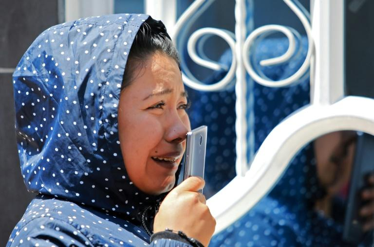 A crying relative of an inmate speaks on a mobile phone outside the La Modelo prison after rioting claimed the lives of 23 inmates and wounded dozens, on March 22, 2020