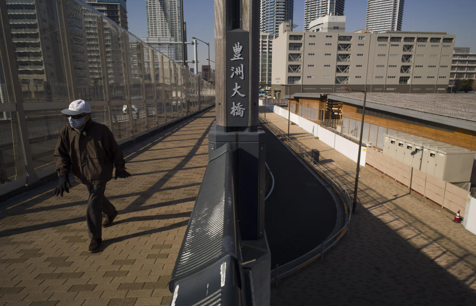 A man walks on a bridge past a closed building complex, right, built to be used for the athletes' village during the rescheduled Tokyo Olympics, in Tokyo on Thursday, Jan. 21, 2021. The postponed Tokyo Olympics are to open in just six months. Local organizers and the International Olympic Committee say they will go ahead on July 23. But it's still unclear how this will happen with virus cases surging in Tokyo and elsewhere around the globe. (AP Photo/Hiro Komae)