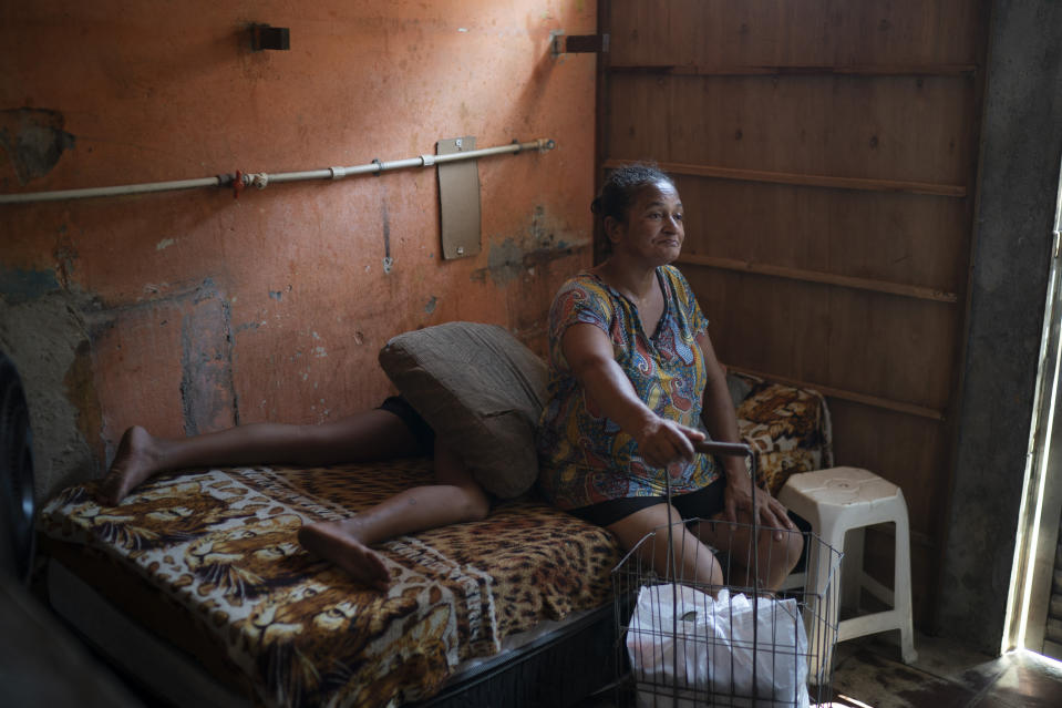 Sandra Brito, 55, sits on her bed after carrying a grocery caddy filled with food donated by the Rio de Paz NGO amid the COVID-19 pandemic in the Mandela slum, in Rio de Janeiro, Brazil, Saturday, March 27, 2021. (AP Photo/Felipe Dana)