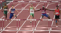 Karsten Warholm, of Norway, second left, clears the final hurdle to beat Rai Benjamin, of United States to win a semifinal of the men's 400-meter hurdles at the 2020 Summer Olympics, Sunday, Aug. 1, 2021, in Tokyo, Japan. (AP Photo/Charlie Riedel)