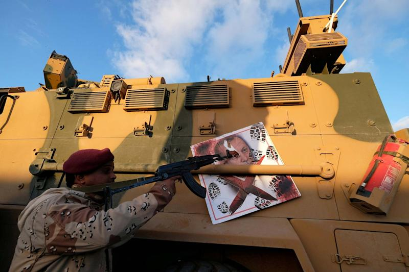 A member of the Libyan National Army (LNA) points his gun to an image of Turkish President Tayyip Erdogan on a Turkish military armored vehicle: REUTERS