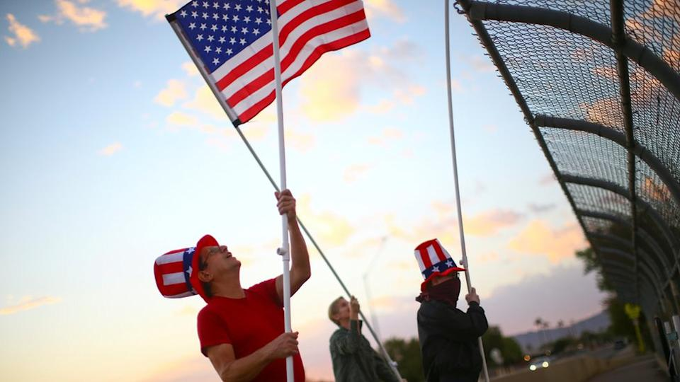 Voters wave U.S flags on a bridge during Election Day in Phoenix