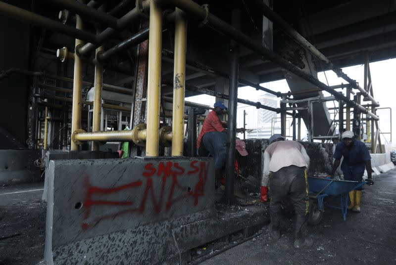Workers clean up the burnt Lekki toll gate in Lagos
