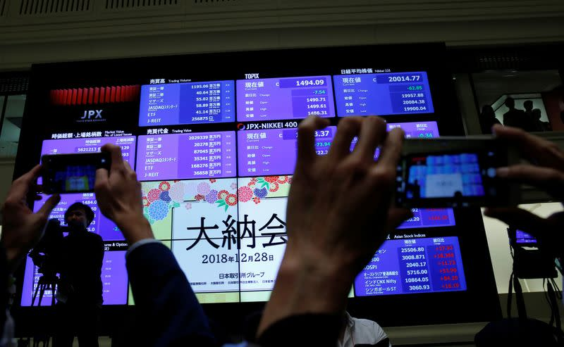 FILE PHOTO: Attendees take pictures of a stock quotation board after a ceremony marking the end of trading in 2018 at the Tokyo Stock Exchange (TSE) in Tokyo