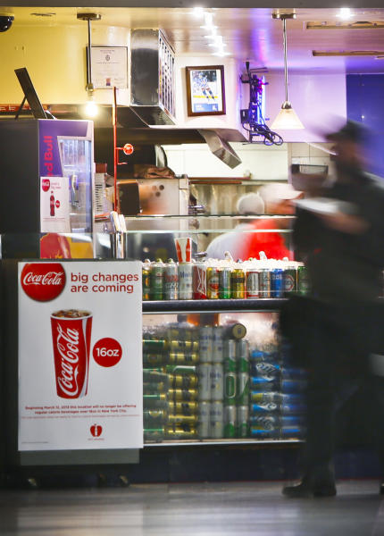 FILE - In this March 8, 2013 file photo, a Coca-Cola poster about the city's anticipated beverage ban is displayed at a pizza shop at New York's Penn Station. New York City's groundbreaking limit on the size of sugar-laden drinks has been struck down by a judge shortly before it was set to take effect. The restriction was supposed to start Tuesday, March 12, 2013. The rule prohibits selling non-diet soda and some other sugary beverages in containers bigger than 16 ounces. It applies at places ranging from pizzerias to sports stadiums, though not at supermarkets or convenience stores. (AP Photo/Bebeto Matthews)