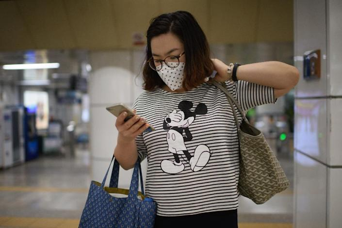 A woman wearing a face masks looks at her phone as she exits a subway station in the popular Myeongdong shopping area in Seoul on June 4, 2015 (AFP Photo/Ed Jones)