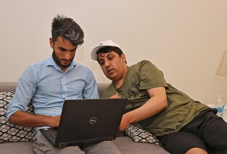Sarhadi and his roommate Khalid Andish spend much of their time tracking news from Afghanistan (AFP/Karim JAAFAR)