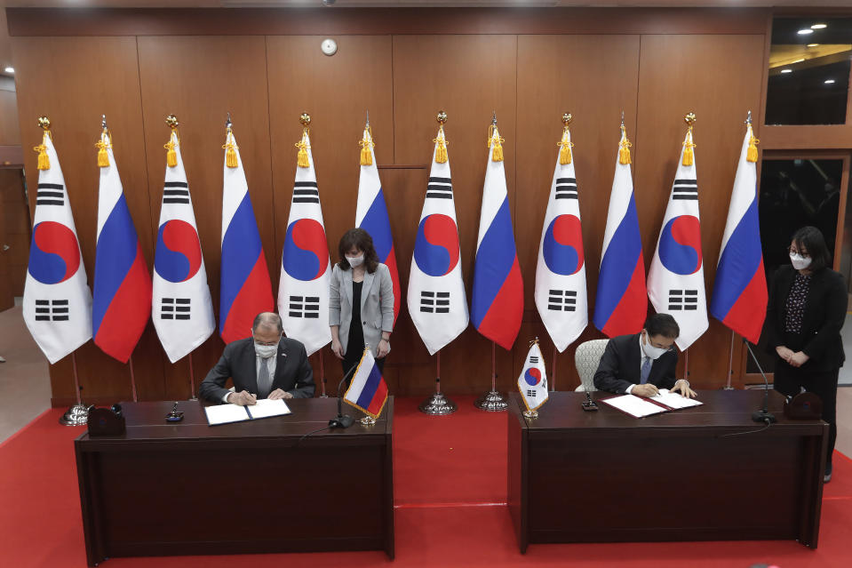 Russian Foreign Minister Sergey Lavrov, left, and South Korean Foreign Minister Chung Eui-yong, second from right, sign an agreement to strengthen the bilateral ties during a joint announcement at the Foreign Ministry in Seoul, South Korea, Thursday, March 25, 2021. (AP Photo/Ahn Young-joon, Pool)