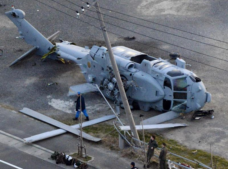 A U.S. Navy MH-60 helicopter lies on the ground after making an emergency landing in Miura city, near Tokyo, Monday, Dec. 16, 2013. U.S. Forces Japan spokesman David Honchul said two injured crew members from the helicopter were taken to a hospital for treatment. Kyodo News agency said one suffered a broken leg and the other had bruises. (AP Photo/Kyodo News) JAPAN OUT, MANDATORY CREDIT