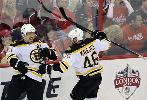 Boston Bruins defenseman Andrew Ference (21) celebrates his goal with David Krejci (46), of the Czech Republic, during the third period of Game 6 of an NHL hockey Stanley Cup first-round playoff series against the Washington Capitals, Sunday, April 22, 2012, in Washington. (AP Photo/Nick Wass)