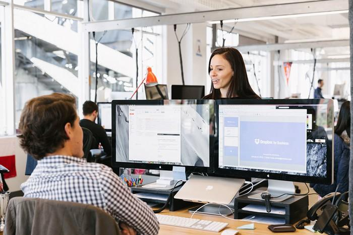 Two workers in an office with Dropbox running across two monitors.