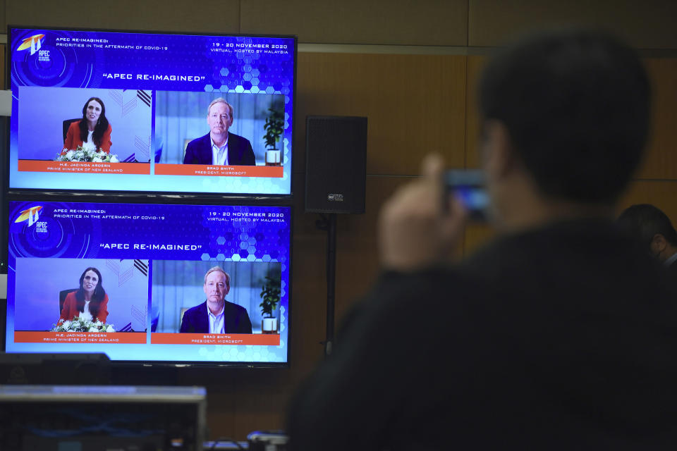 In this photo released by Malaysia Department of Information, screens show New Zealand's Prime Minister Jacinda Ardern, left, and Microsoft President Brad Smith speak via virtual meeting during the APEC CEO Dialogues 2020, ahead of the Asia-Pacific Economic Cooperation (APEC) leaders' summit in Kuala Lumpur, Malaysia, Friday, Nov. 20, 2020. (Fandy Azlan/Malaysia Department of Information via AP)
