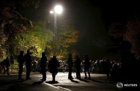 Migrants wait at the Austrian-German border in Achleiten, Austria, across from Passau, Germany October 29, 2015. REUTERS/Michaela Rehle