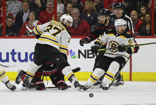 Boston Bruins' Patrice Bergeron (37) and Brad Marchand (63) skate for the puck with Carolina Hurricanes' Brett Pesce (22) and Jordan Staal during the second period in Game 3 of the NHL hockey Stanley Cup Eastern Conference final series in Raleigh, N.C., Tuesday, May 14, 2019. (AP Photo/Gerry Broome)