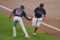 Boston Red Sox' Kyle Schwarber, right, is greeted by third base coach Carlos Febles (52) as he rounds the bases on his home run during the second inning of a baseball game against the Baltimore Orioles, Tuesday, Sept. 28, 2021, in Baltimore. (AP Photo/Nick Wass)