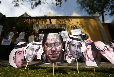 A picture of Saudi blogger Raif Badawi  is seen between others photos of prisoners in Saudi Arabia during a demonstration for his release from jail outside Embassy of Saudi Arabia in Mexico City