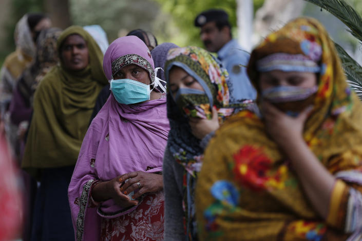 Women in Islamabad, Pakistan, wait to receive cash from a government program for families in need