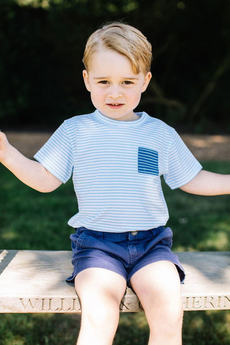 """<p>Prince George rocks stripes and shorts at this sweet summer shoot at his family's Norfolk home in July 2016. The swing he sits on is engraved with his parents' names, """"William & Catherine.""""</p>"""