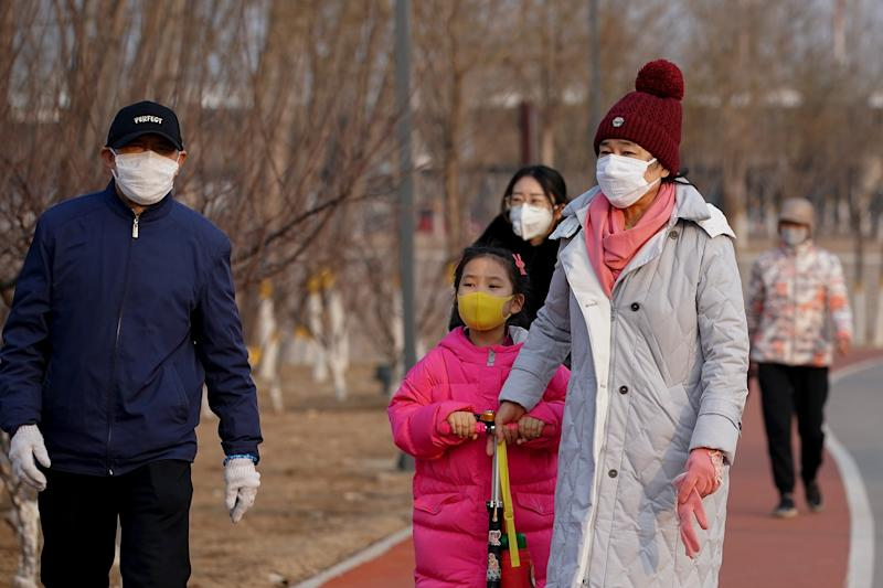 People wear face masks during a visit to a park in Beijing on Feb. 29, 2020.