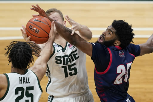 Detroit Mercy guard Marquell Fraser (25) and Michigan State forwards Thomas Kithier (15) and Malik Hall (25) reach for a rebound during the second half of an NCAA college basketball game Friday, Dec. 4, 2020, in East Lansing, Mich. (AP Photo/Carlos Osorio)