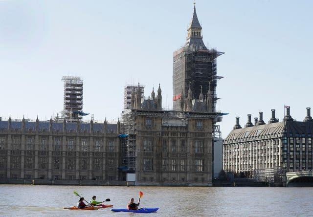 Canoeists pass The Houses of Parliament on the River Thames