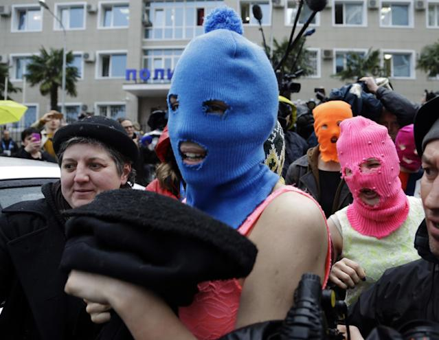 Russian punk group Pussy Riot members Nadezhda Tolokonnikova, in the blue balaclava, and Maria Alekhina, in the pink balaclava, make their way through a crowd after they were released from a police station, Tuesday, Feb. 18, 2014, in Adler, Russia. No charges were filed against Tolokonnikova and Alekhina along with the three others who were held. (AP Photo/Morry Gash)