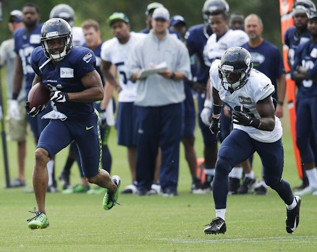Seattle Seahawks wide receiver Percy Harvin, left, runs with the ball after making a catch as free safety Steven Terrell, right, pursues, Saturday, Aug. 2, 2014, during NFL football training camp in Renton, Wash. (AP Photo/Ted S. Warren)