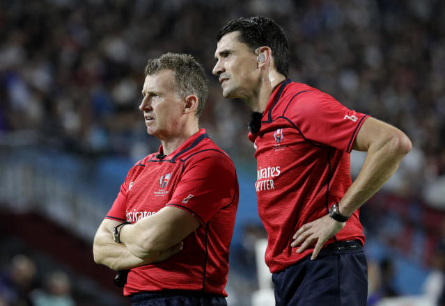 Referee Pascal Gauzere and and assistant Nigel Owens, left, watch a video review before awarding Scotland a penalty try during the Rugby World Cup Pool A game at Kobe Misaki Stadium between Scotland and Samoa in Kobe City, Japan, Monday, Sept. 30, 2019. (AP Photo/Aaron Favila)