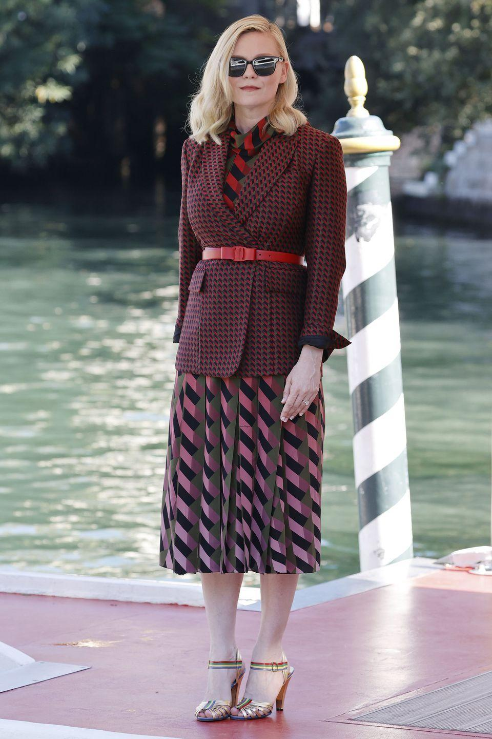 <p>Kirsten Dunst dressed for the autumnal months in a burgundy checked blazer and pleated skirt by Salvatore Ferragamo. </p>