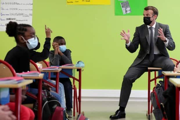 Macron talks with pupils during a visit to a school in Melun on April 26, 2021.