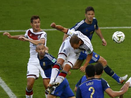 Germany's Benedikt Hoewedes (top) misses a chance to score during their 2014 World Cup final against Argentina at the Maracana stadium in Rio de Janeiro July 13, 2014. REUTERS/Ricardo Moraes