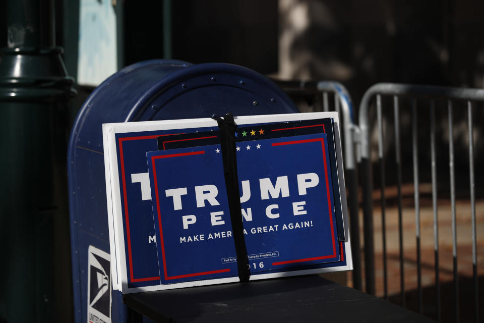 Trump signs sit beside a mailbox as supporters of President Donald Trump set up to protest outside the Pennsylvania Convention Center, where vote counting continues, in Philadelphia, Monday, Nov. 9, 2020, two days after the 2020 election was called for Democrat Joe Biden.(AP Photo/Rebecca Blackwell)