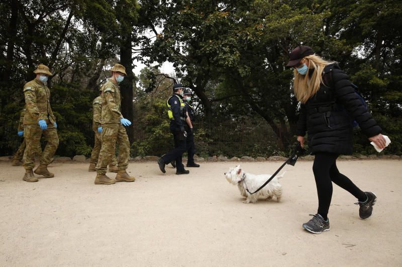 A woman walks her dog as ADF personnel and Victorian police officers pass in a central Melbourne park. Source: AAP