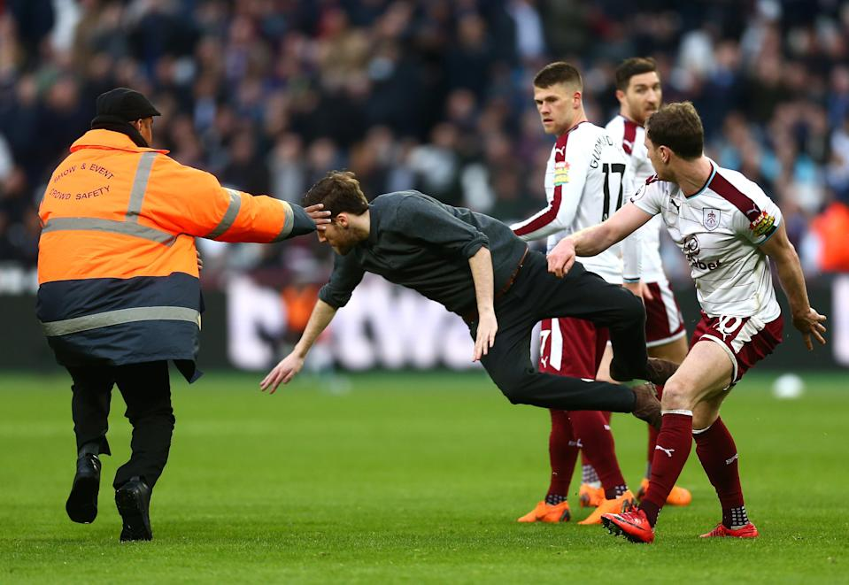 A fan is sent flying by a Burnley player. (Getty)