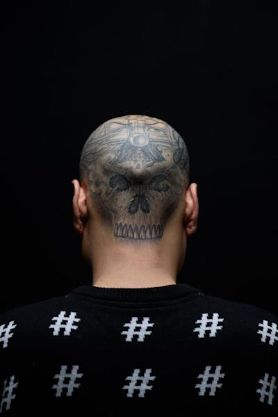 Tattoo artist 'Six' poses for a photo at the Tattooism tattoo studio in Seoul on December 14, 2014 (AFP Photo/Ed Jones)