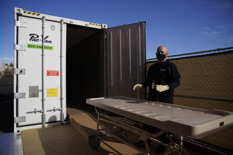 FILE - In this Jan. 8, 2021, file photo, Michael Murphy, a consultant serving as interim Clark County coroner, gives a tour of a refrigerated trailer at the coroner's office in Las Vegas. As in other cities, some overwhelmed funeral homes have used refrigerated trailers to hold the dead, Murphy said. (AP Photo/John Locher, File)
