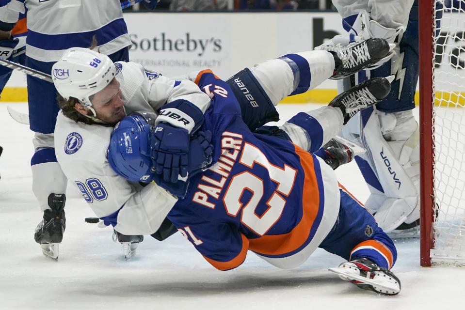 CORRECTS ID TO KYLE PALMIERI (21) NOT OTTO KOIVULA - Tampa Bay Lightning defenseman Mikhail Sergachev (98) and New York Islanders left wing Kyle Palmieri (21) fight during the second period of Game 3 of the NHL hockey Stanley Cup semifinals, Thursday, June 17, 2021, in Uniondale, N.Y. (AP Photo/Frank Franklin II)