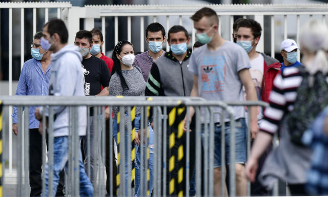 Workers at the Toennies meatpacking plant in Rheda-Wiedenbrueck, Germany, where hundreds of staff have tested positive for coronavirus (AP)