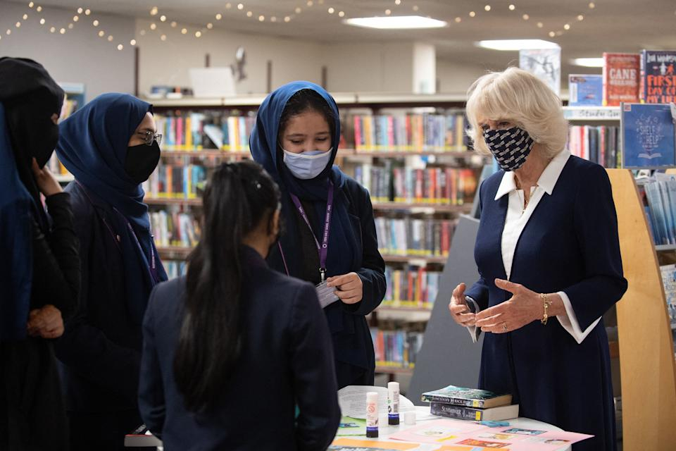 Britain's Camilla, Duchess of Cornwall, wearing a face covering to combat the spread of Covid-19, meets pupils from Eden Girls' School during her visit to Coventry Central Library in Coventry, central England on May 25, 2021. (Photo by Joe Giddens / POOL / AFP) (Photo by JOE GIDDENS/POOL/AFP via Getty Images)