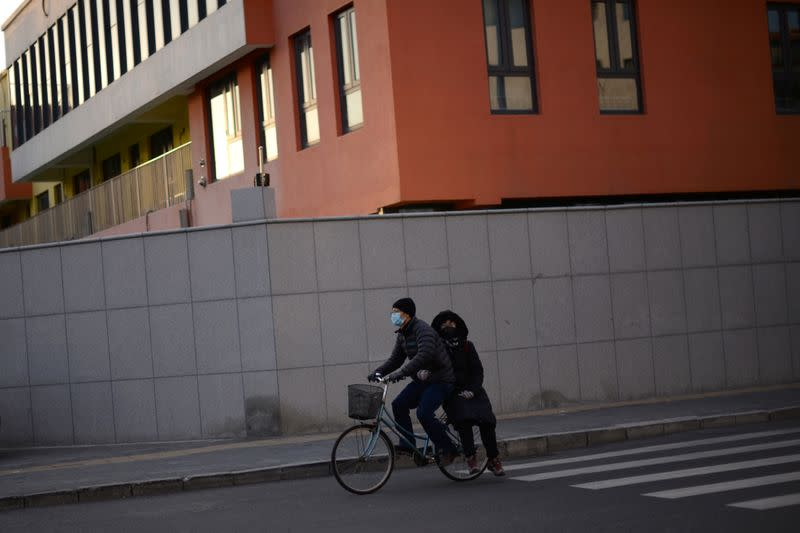 A man wearing a face mask rides a bicycle with a passenger on the back, in Beijing