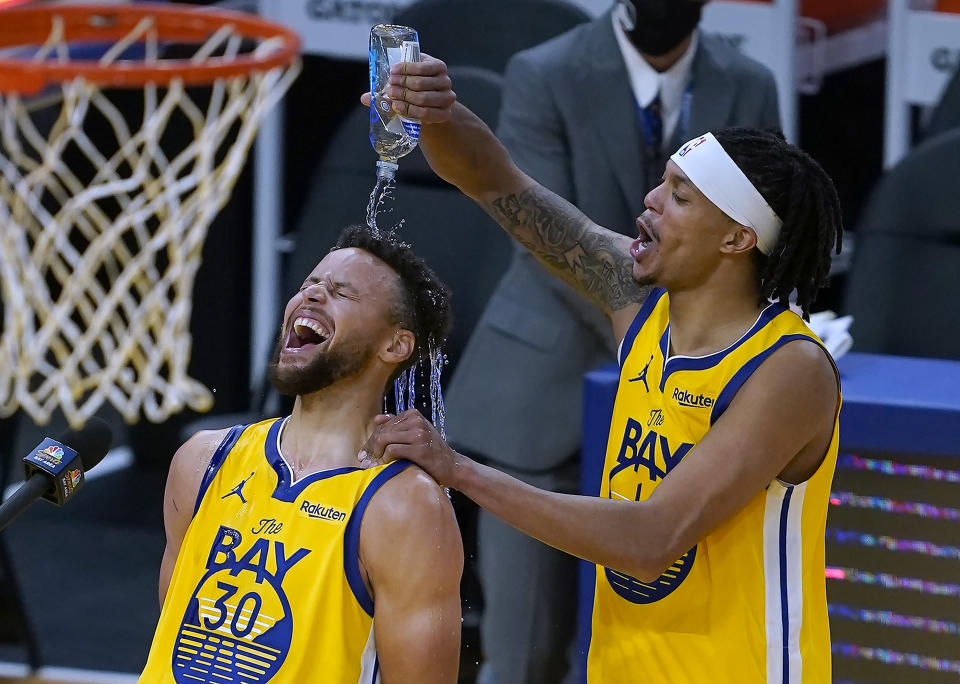 Golden State Warriors guard Damion Lee, right, pours water over the head of guard Stephen Curry (30) while celebrating Curry's career-high 62 points against the Portland Trail Blazers in an NBA basketball game in San Francisco, Sunday, Jan. 3, 2021. (AP Photo/Tony Avelar)
