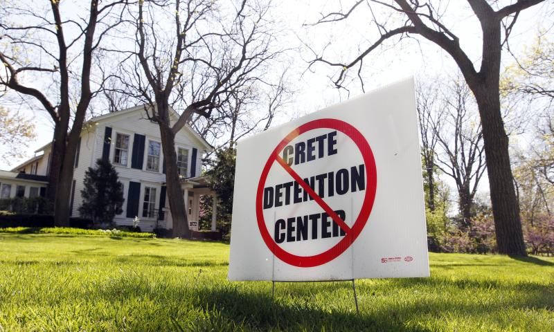 This Wednesday, April 11, 2012 photo shows a home in Crete, Ill., with an anti-detention center sign on the lawn in the community that is considering a proposal by U.S. Immigration and Customs Enforcement and a private company for a nearly 800-bed immigrant detention facility. The proposal could be stopped if a measure in the Illinois Legislature, which extends the state's ban on privately-contracted jails, passes the state House in the coming weeks. (AP Photo/M. Spencer Green