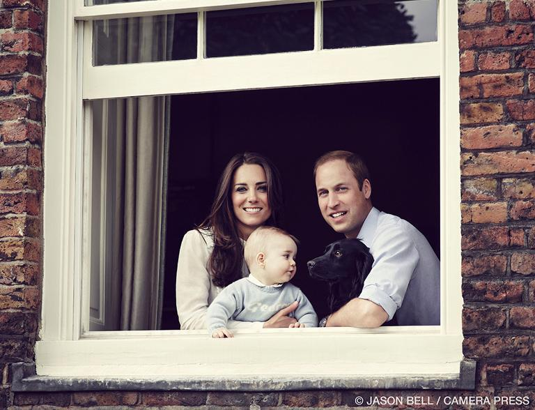 Britain's Prince William and Catherine, Duchess of Cambridge pose with their son Prince George and pet dog Lupo at their residence in Kensington Palace in mid March 2014