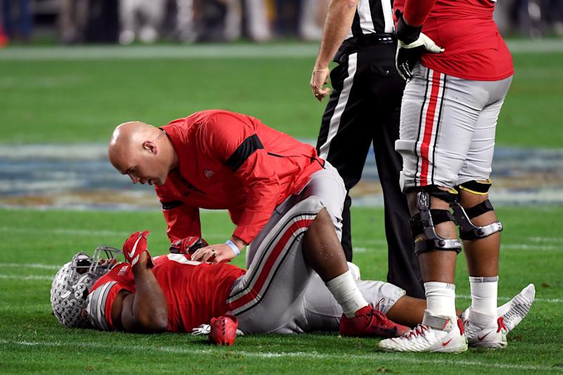 GLENDALE, ARIZONA - DECEMBER 28: J.K. Dobbins #2 of the Ohio State Buckeyes is checked by the trainer against the Clemson Tigers in the first half during the College Football Playoff Semifinal at the PlayStation Fiesta Bowl at State Farm Stadium on December 28, 2019 in Glendale, Arizona. (Photo by Norm Hall/Getty Images)