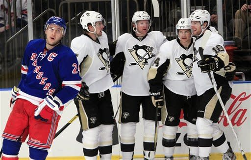 Pittsburgh Penguins' Chris Kunitz, second from right, celebrates with teammates after scoring a goal as New York Rangers' Ryan Callahan, left, skates away during the first period of an NHL hockey game on Thursday, Jan. 19, 2012, in New York. (AP Photo/Frank Franklin II)