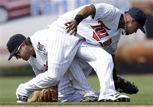 Minnesota Twins shortstop Pedro Florimon, right, hangs on to a pop fly by Toronto Blue Jays' Andy LaRoche after teammate second baseman Brian Dozier, left, crashed into him during the fifth inning of an exhibition spring training baseball game in Fort Myers, Fla., Sunday, March 24, 2013. (AP Photo/Elise Amendola)