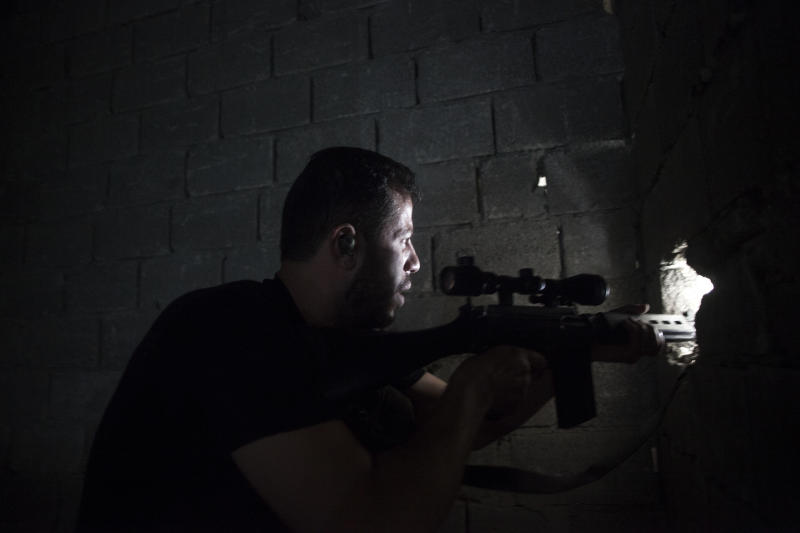 Free Syrian Army fighter scans for targets from a building in Aleppo, Syria, Thursday, Sept. 27, 2012. (AP Photo/ Manu Brabo)