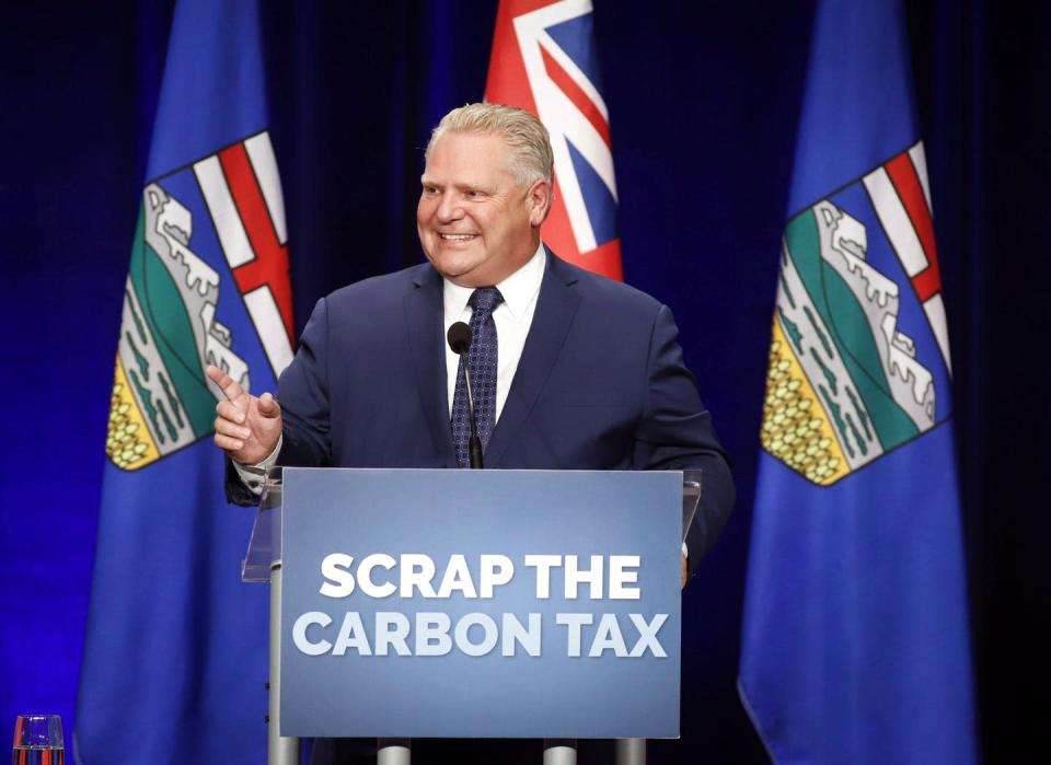 Doug Ford stands behind a podium with a sign reading 'Scrap the carbon tax'