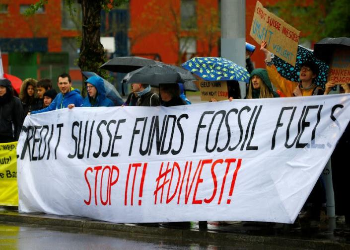 FILE PHOTO: Climate protestors display a banner outside the venue where Swiss bank Credit Suisse holds the company's annual shareholder meeting in Zurich