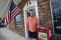 Roger West, columnist of the Westside Journal in northeast Florida outside the entrance to the newspaper office Tuesday, Aug. 10, 2021, in Callahan, Fla. Outspoken as he had been in opposing COVID-19 vaccines he reconsidered after the virus returned with a deadly vengeance in mid-July. (AP Photo/John Raoux)